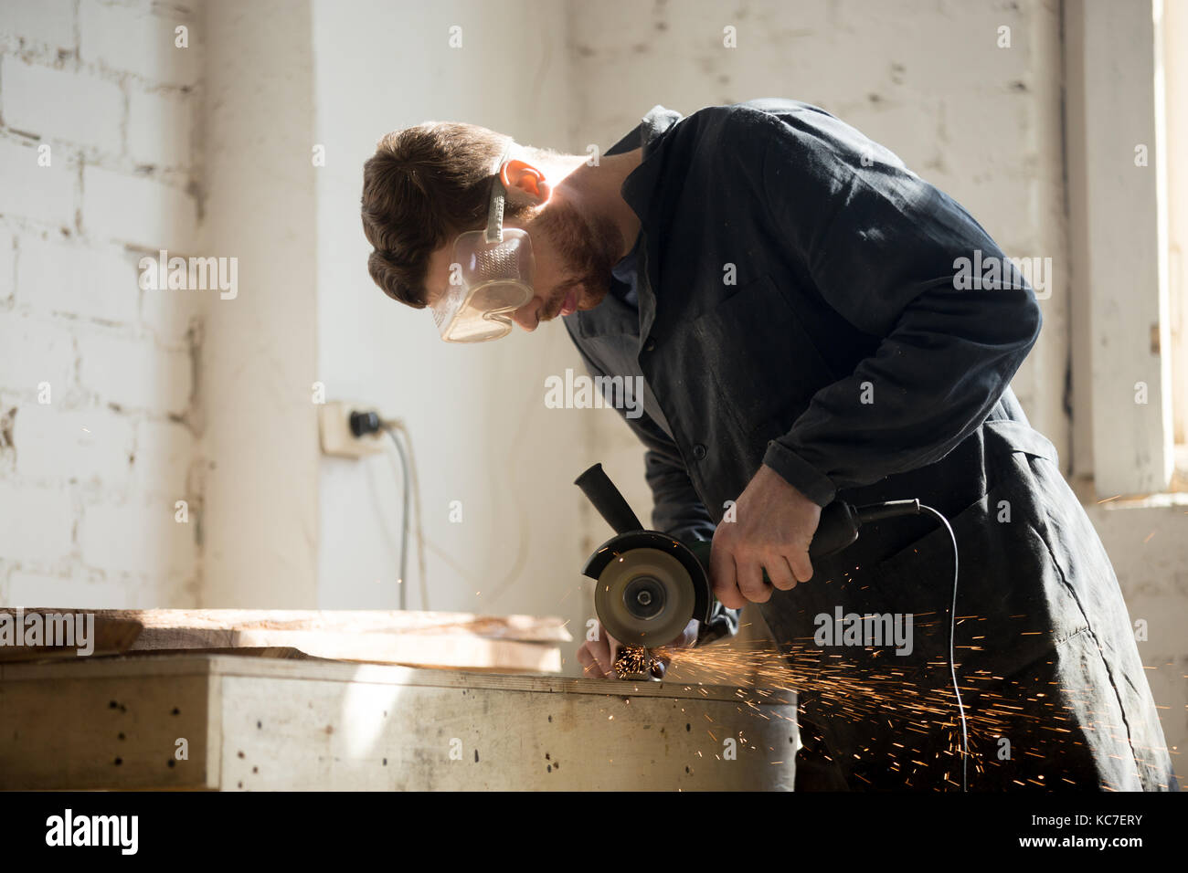 Side view of worker using angle grinder for metal cutting  - Stock Image