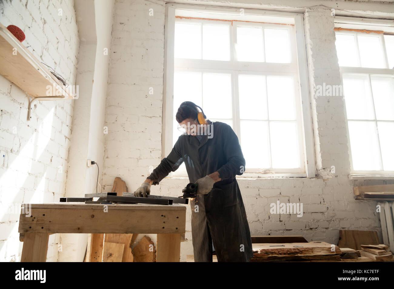 Carpenter works in custom furniture manufacturing - Stock Image