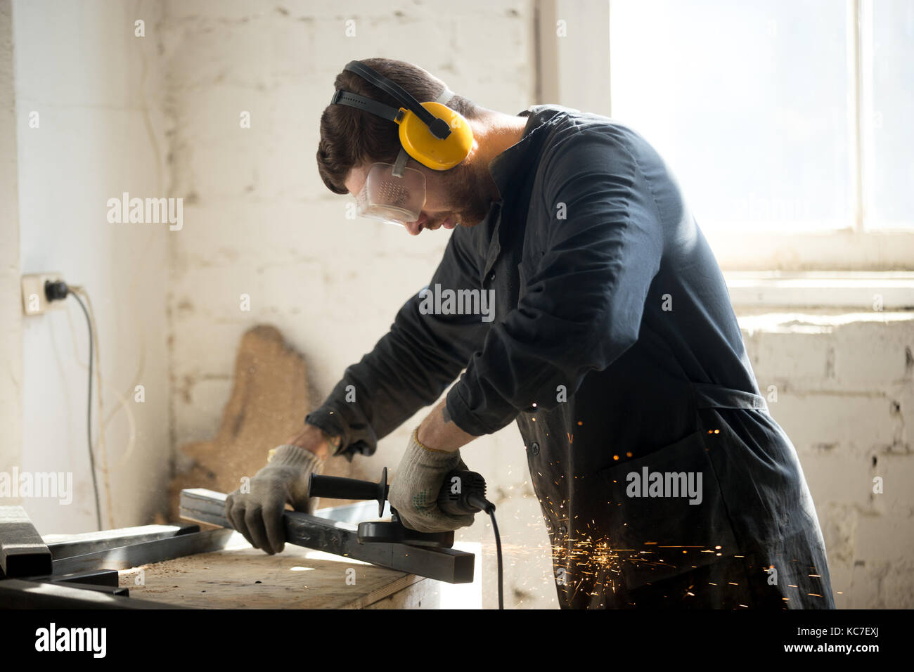 Worker in protective clothes working in workshop - Stock Image