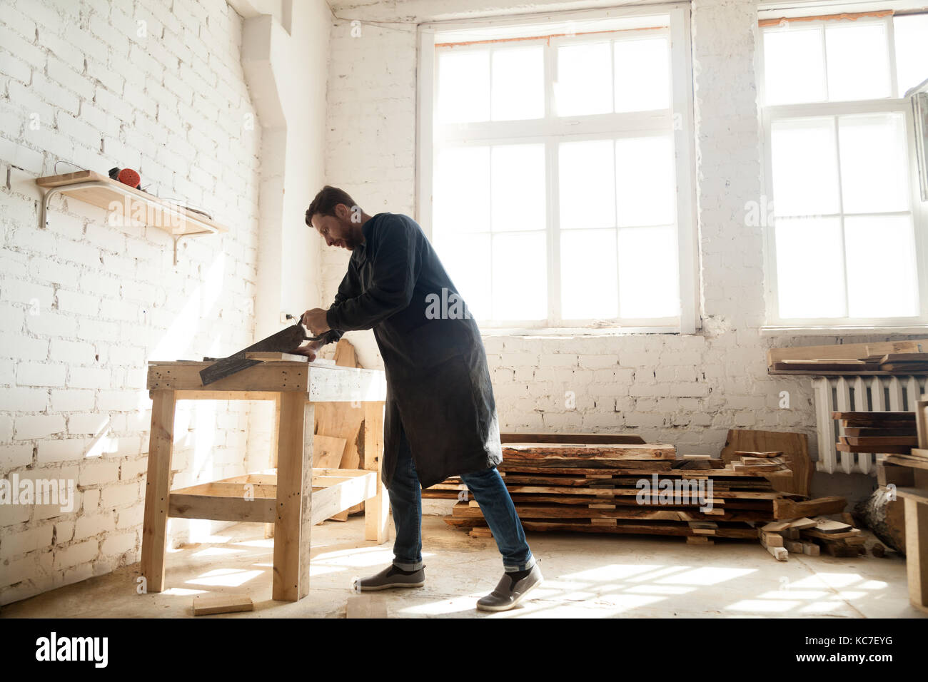 Woodwork and construction. Carpenter using handsaw for sawing wo - Stock Image