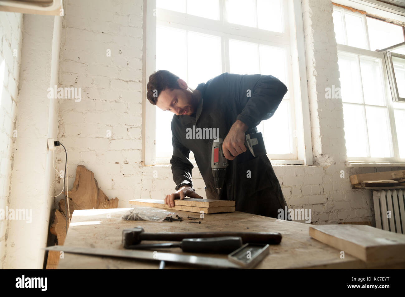 Young carpenter doing woodwork in carpentry - Stock Image
