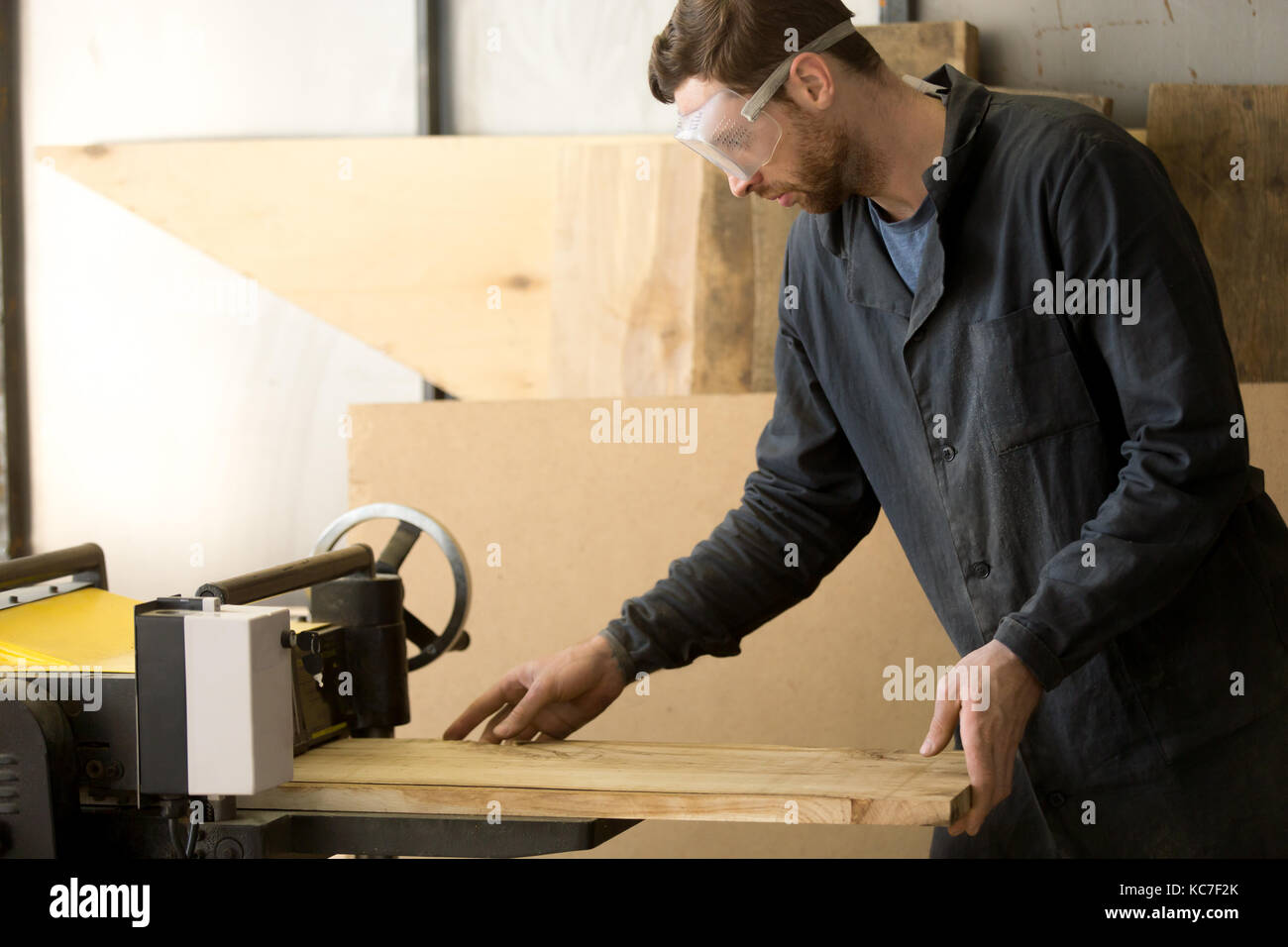 Worker producing lumber on local sawmill - Stock Image