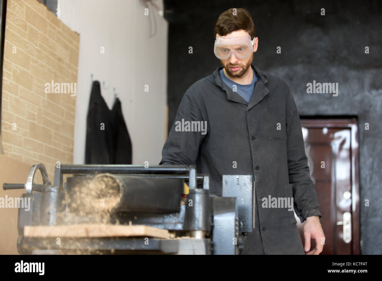 Carpenter in safety glasses works on machine tool - Stock Image