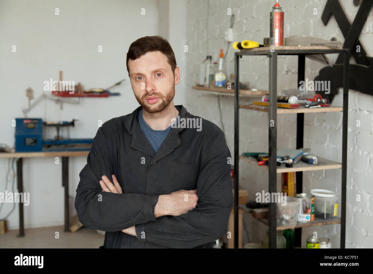 Portrait of serious young handyman standing in own workshop inte - Stock Image