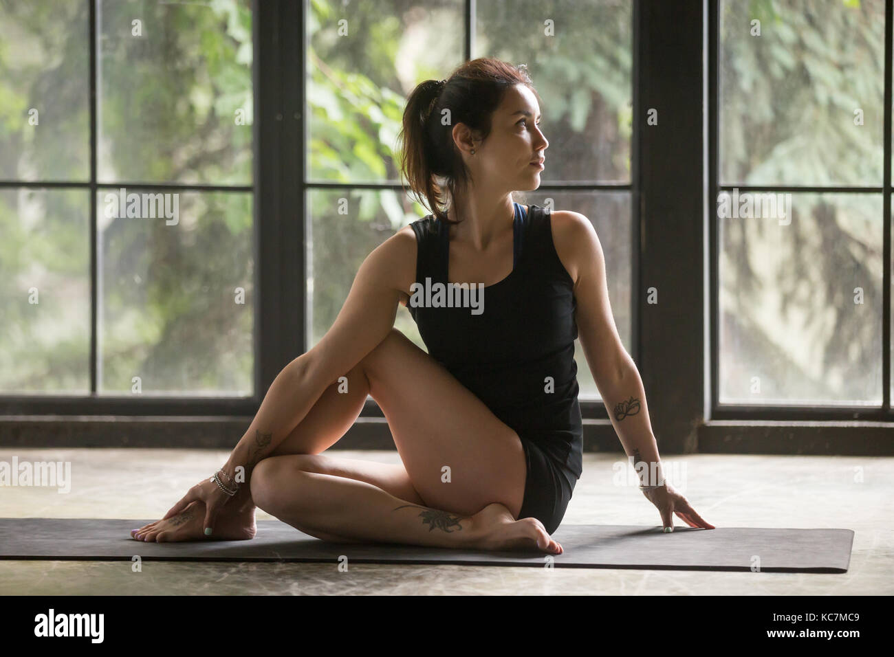 Young attractive woman in Ardha Matsyendrasana pose, studio back - Stock Image