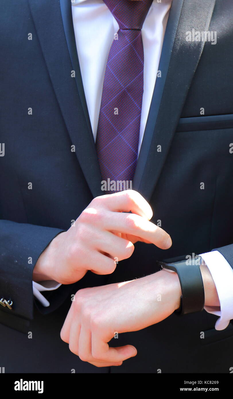 Close-up frontal view of a person in a dark suit, a white shirt and a purple tie setting a black watch  in portrait - Stock Image