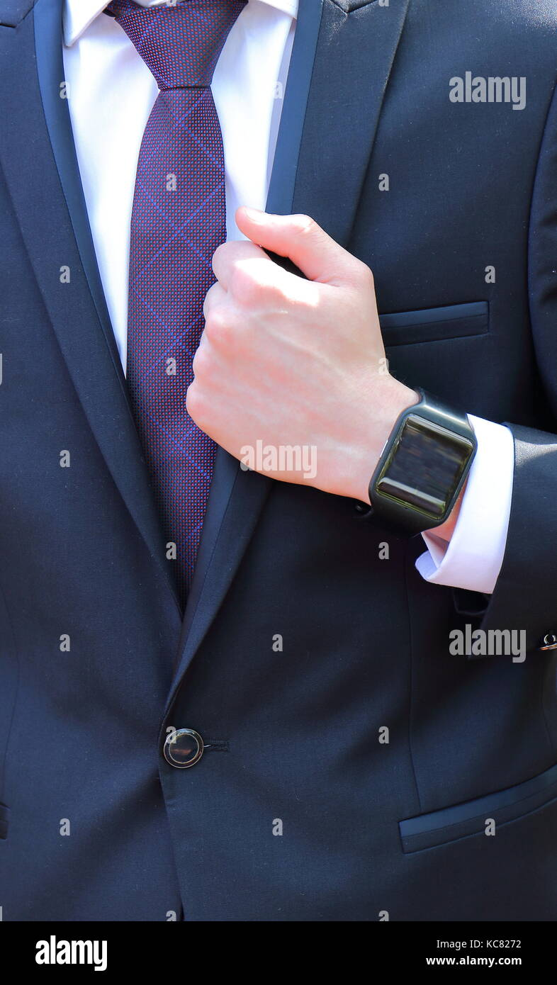 Close-up frontal view of a person in a dark suit, a white shirt, a purple tie and a black watch in portrait format - Stock Image