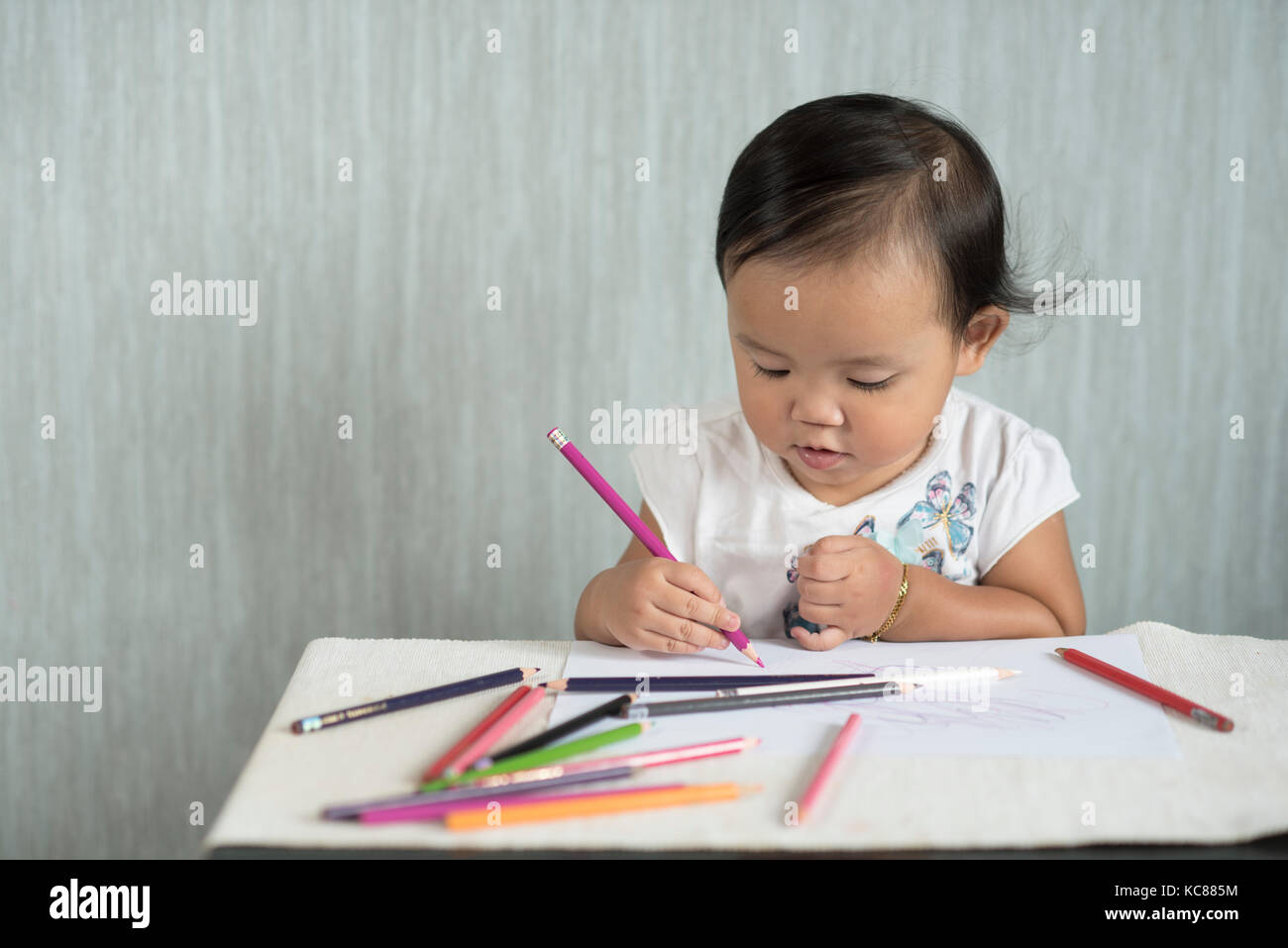 asian toddler / baby girl is having fun learning to use pencils. Education concept. human growth concept. Stock Photo