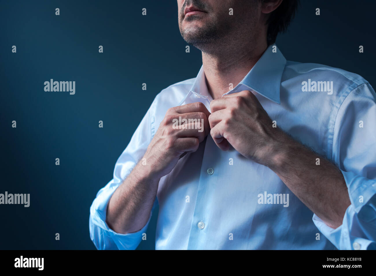 Businessman getting dressed for job interview, man buttoning white shirt - Stock Image