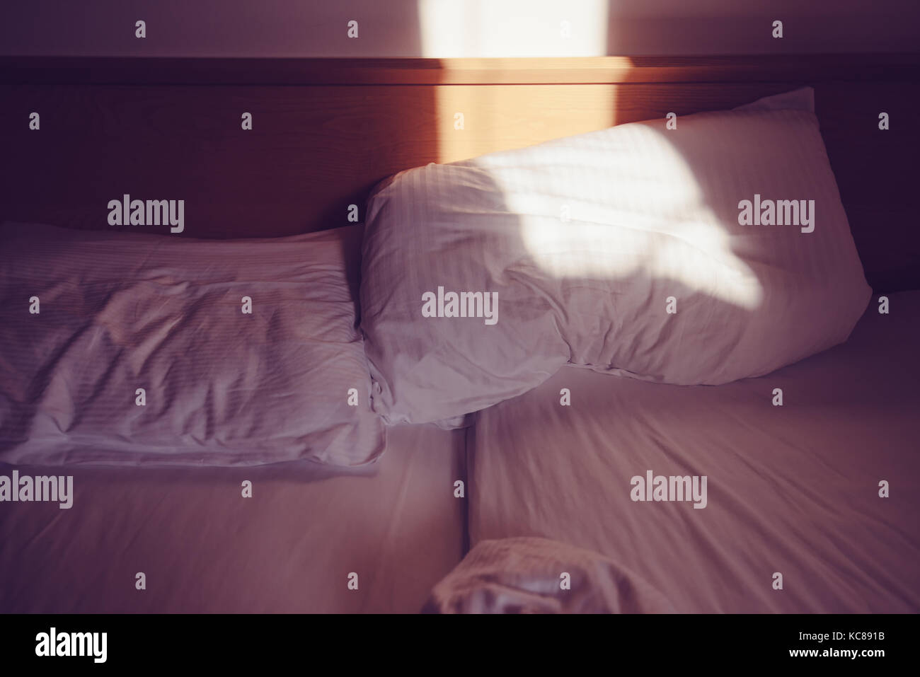 Messy bed in the morning, white pillows in the bedroom with sunlight - Stock Image