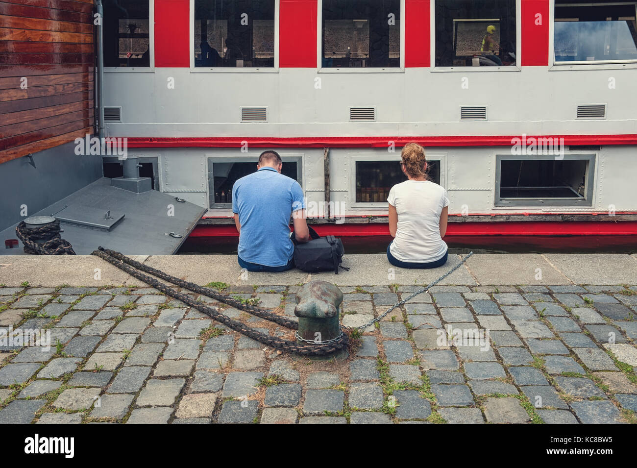 Two unidentified people sitting with their backs to the camera without touching each other. Human relationships. - Stock Image
