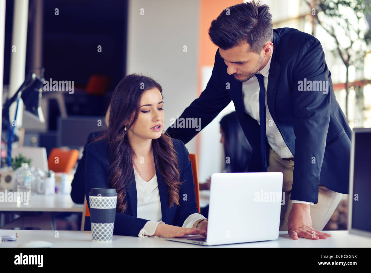 startup business concept with young multiethnic couple in modern office working on laptop - Stock Image