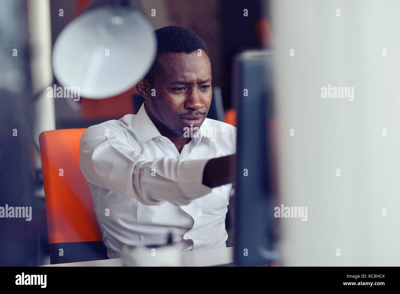 Disappointed African businessman is dazed and confused by a mistake in official documents. - Stock Image