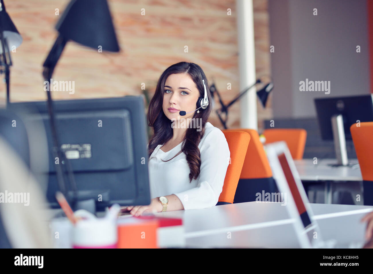 Young woman working in call centre, surrounded by colleagues - Stock Image