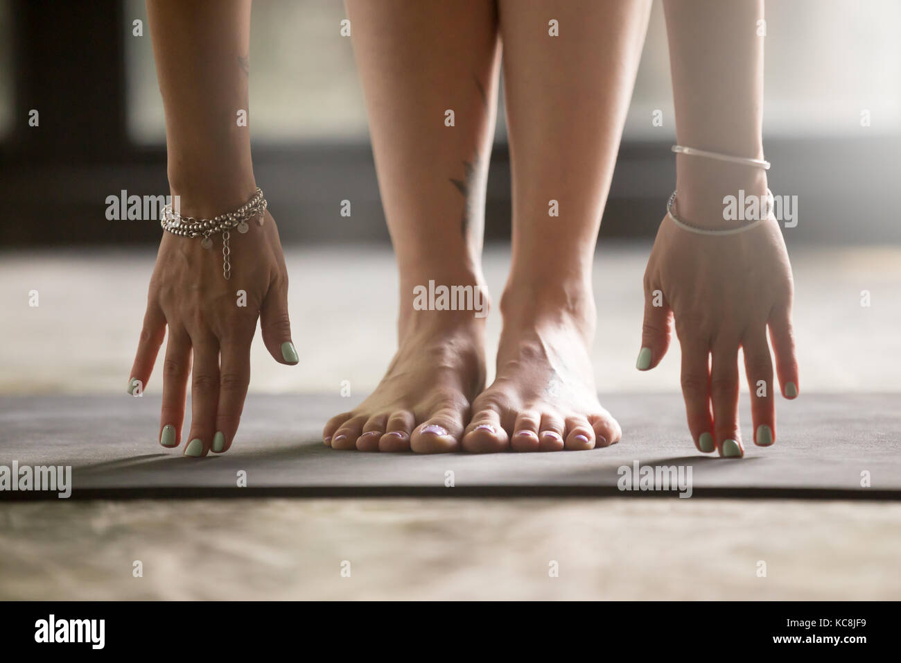Close up of female hands touching yoga mat - Stock Image