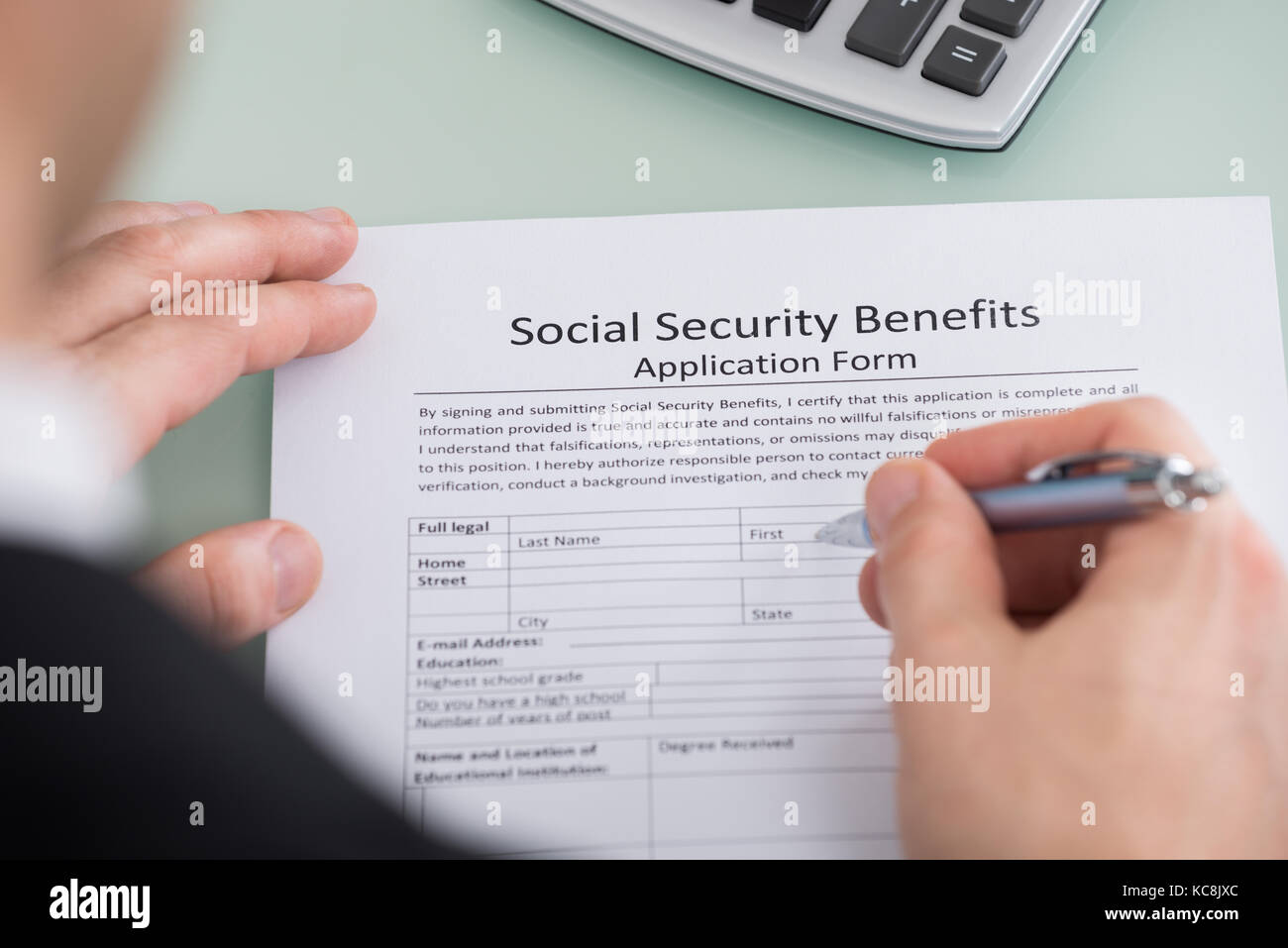 Close-up Of Person Hand Filling Social Security Benefits Form - Stock Image
