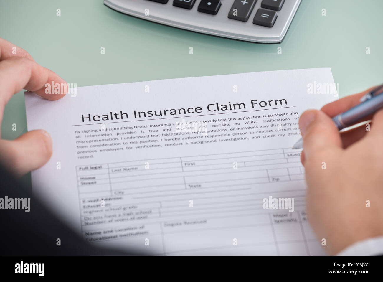 Close-up Of Person Filling Health Insurance Claim Form - Stock Image