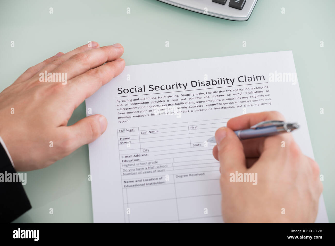Close Up Of Person Hand Over Social Security Disability Claim Form