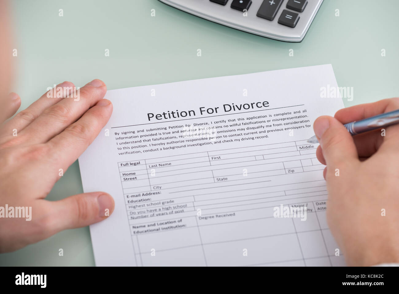 Close-up Of Person Hand Over Petition For Divorce Form - Stock Image