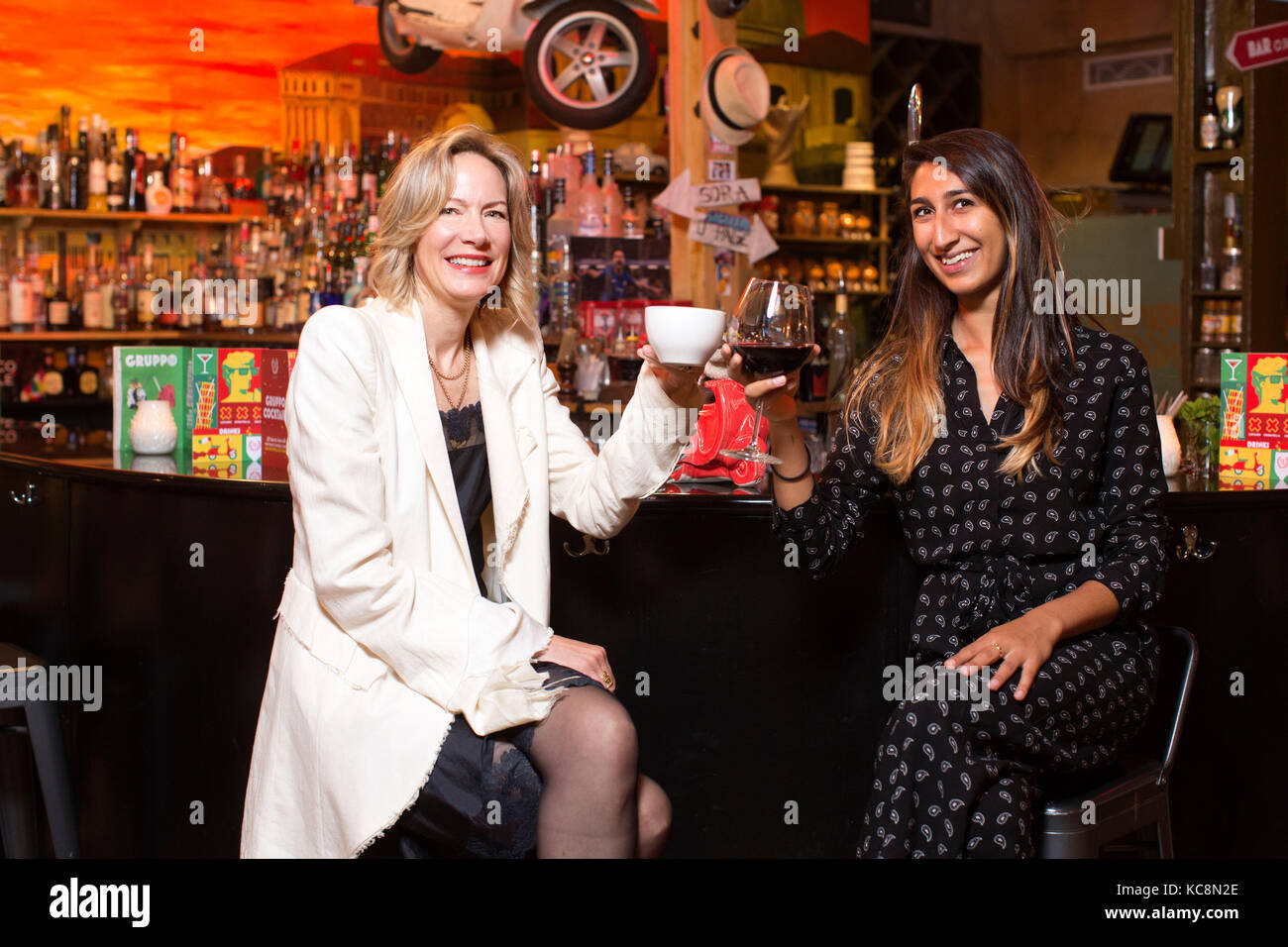 Millennial and a midlifer swapping drinking habits at a local bar in London, UK - Stock Image