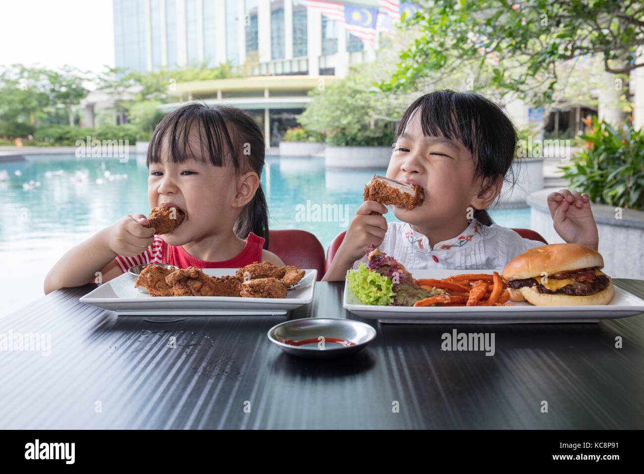 Asian Little Chinese Girls Eating Burger and Fried chicken at Outdoor Cafe - Stock Image