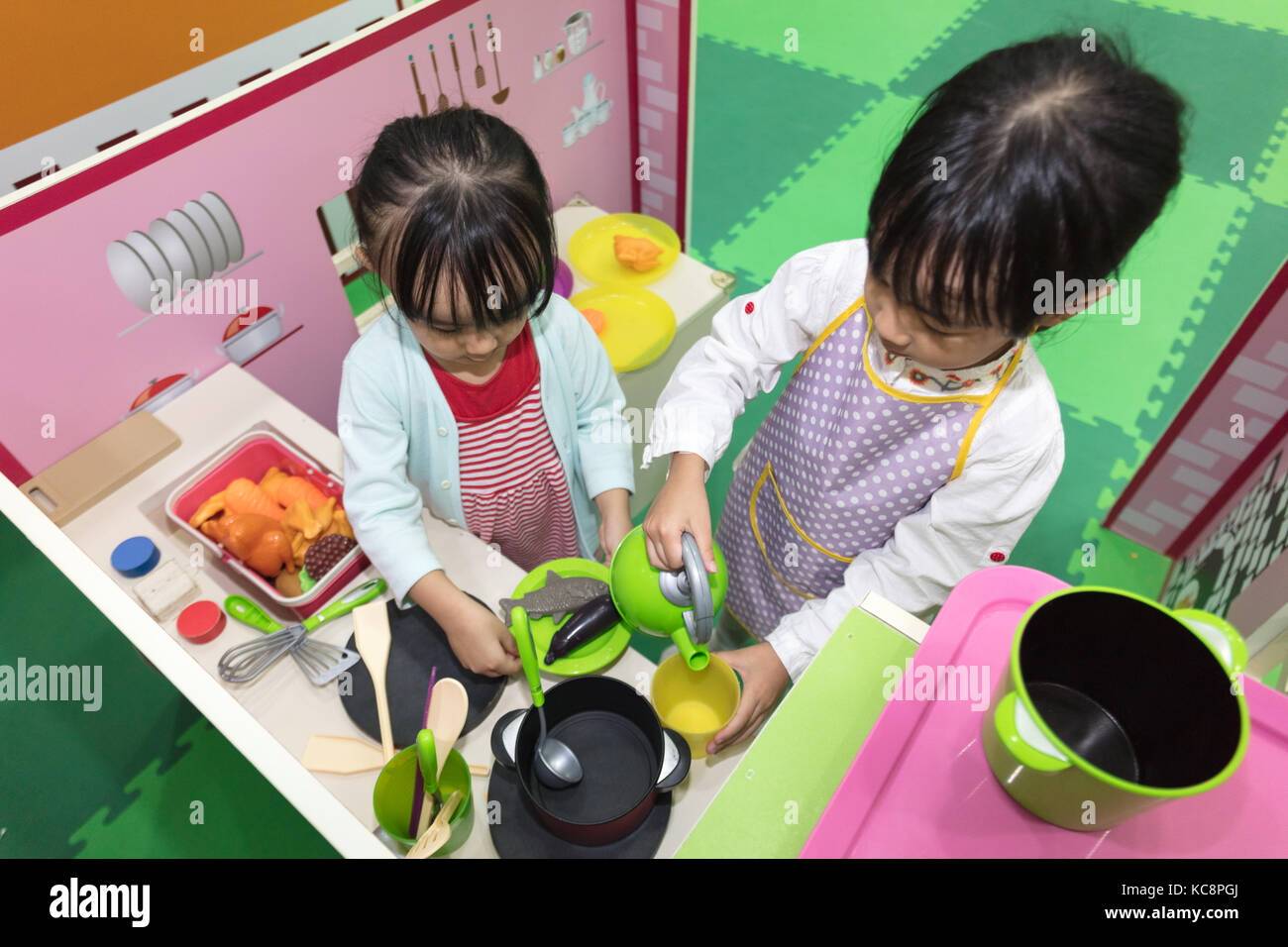 Asian Chinese little girls role-playing at kitchen at indoor playground - Stock Image