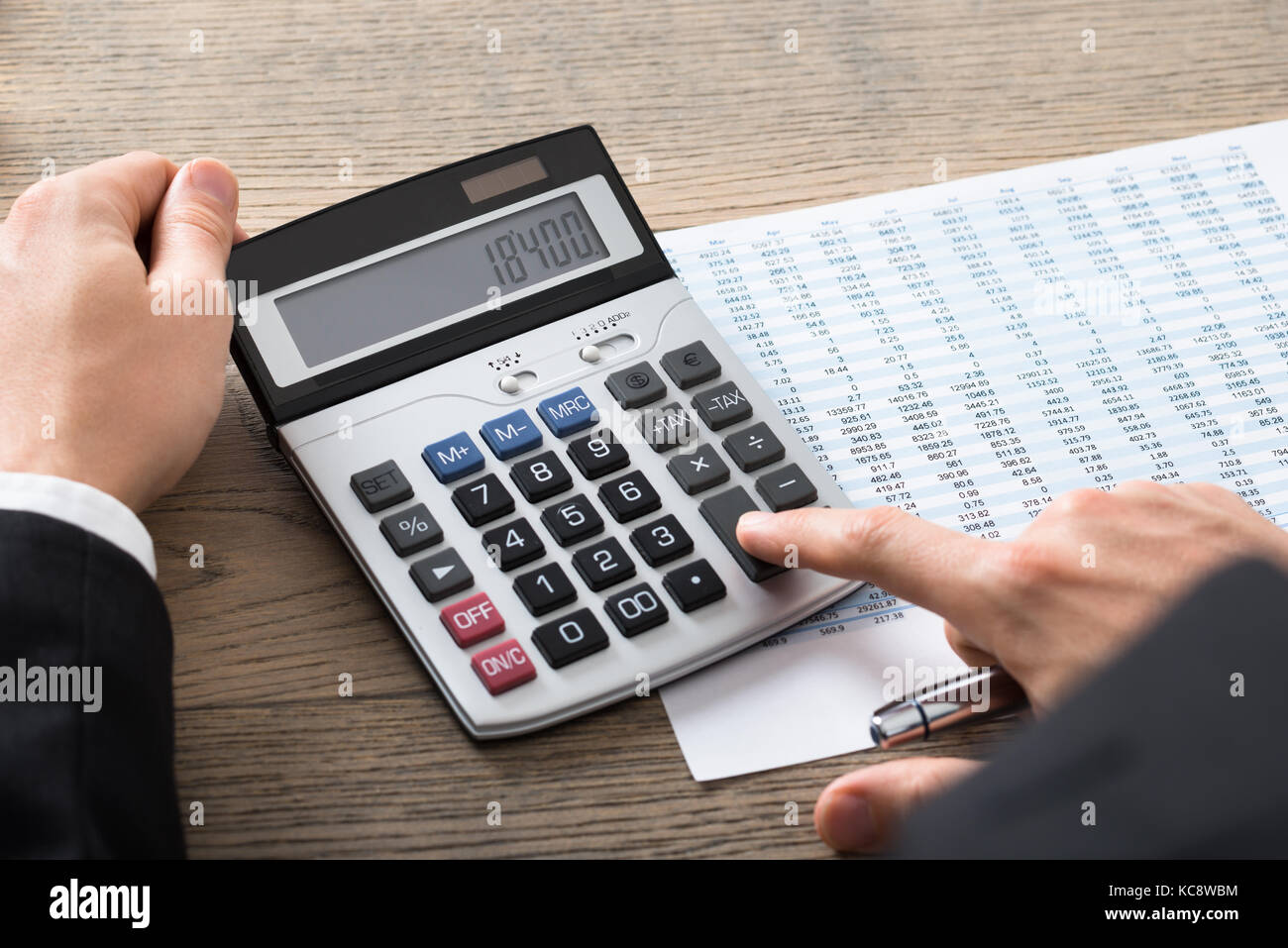 Close-up Of A Businessman Analyzing Accounting Document With Calculator At Desk In Office Stock Photo