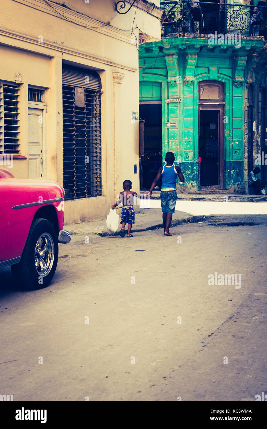 Two Cuban boys walk past a pink painted car. Urban, Havana, Cuba. - Stock Image