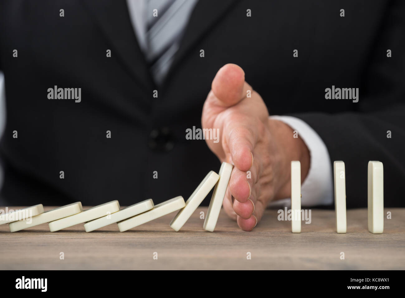 Close-up Of A Businessman Hand Stopping Dominoes From Falling On A Desk In Office - Stock Image