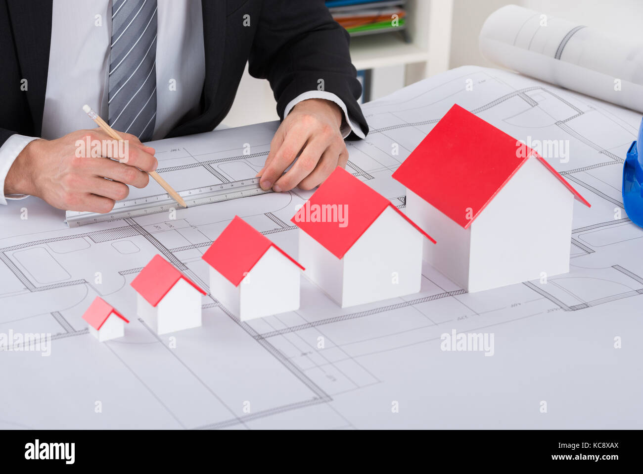Close-up Of Male Architect Hand With House Models Working On Blueprint In Office - Stock Image