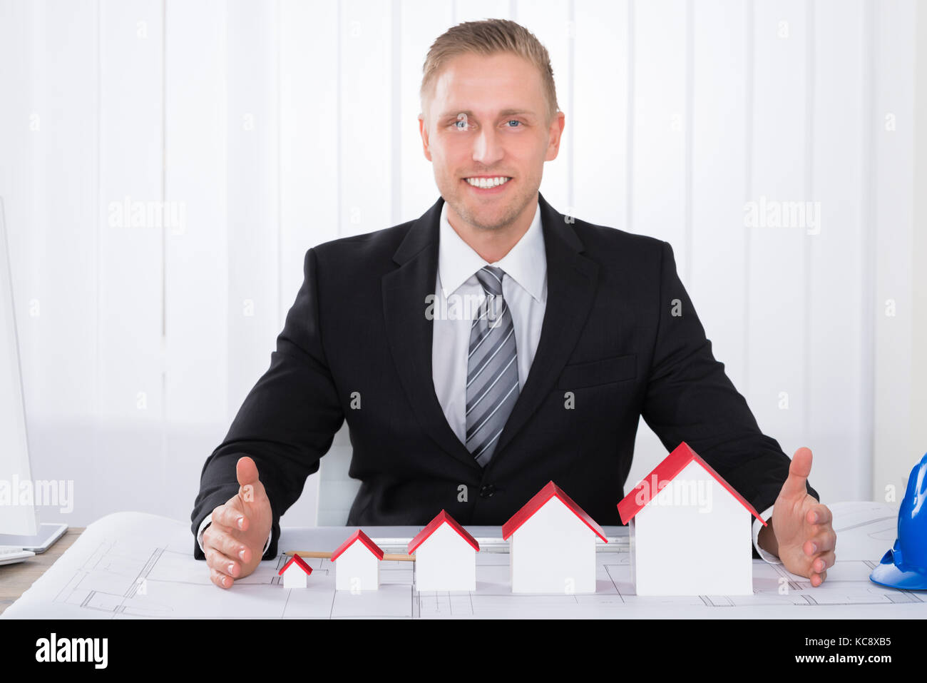 Young Happy Male Architect Working With House Models On Blueprints In Office - Stock Image