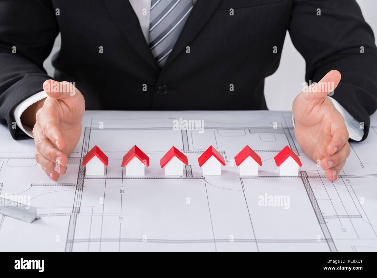 Close-up Of Male Architect Hand Protecting Different Size Of House Models On Blueprint - Stock Image