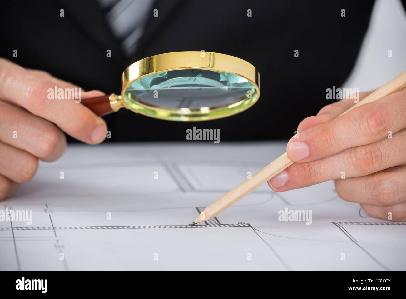 Close-up Of Male Architect Hand Using Magnifying Glass While Working On Blueprint In Office - Stock Image