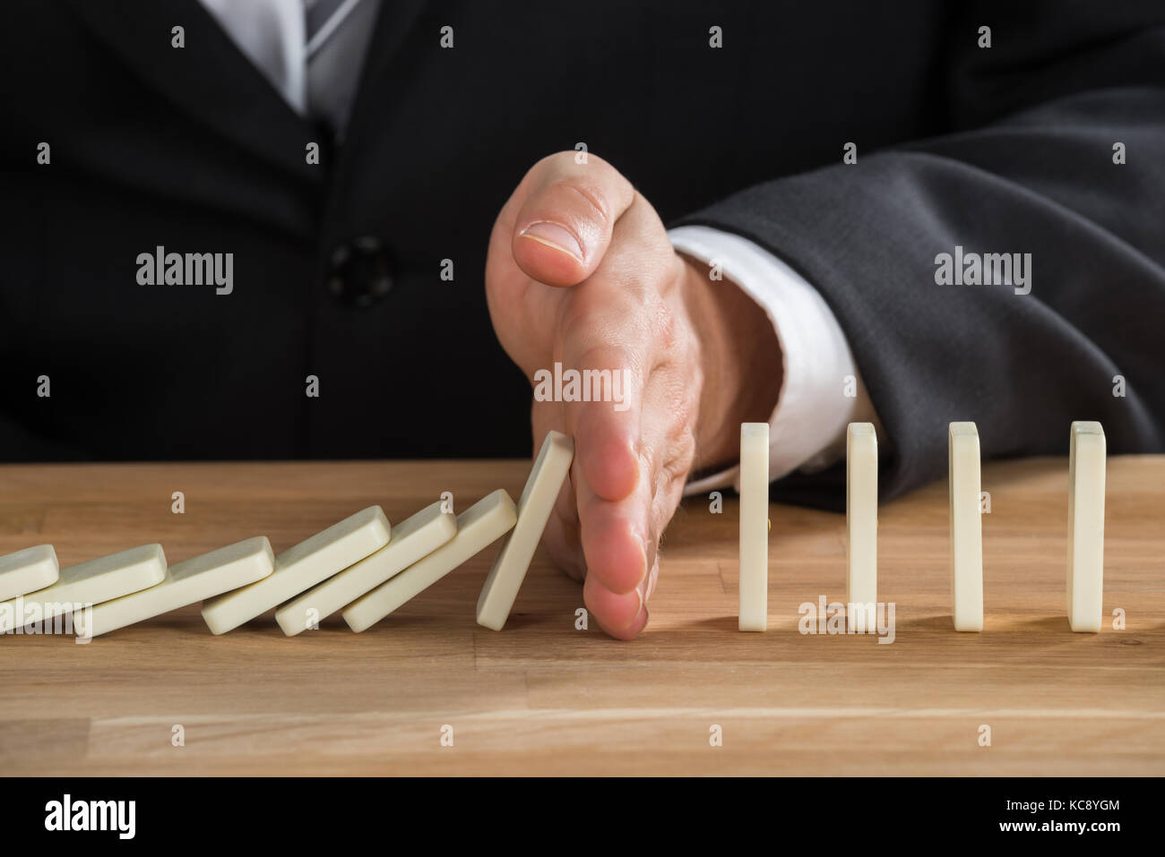 Close-up Of Young Businessperson Stopping Dominos From Falling On Wooden Desk - Stock Image