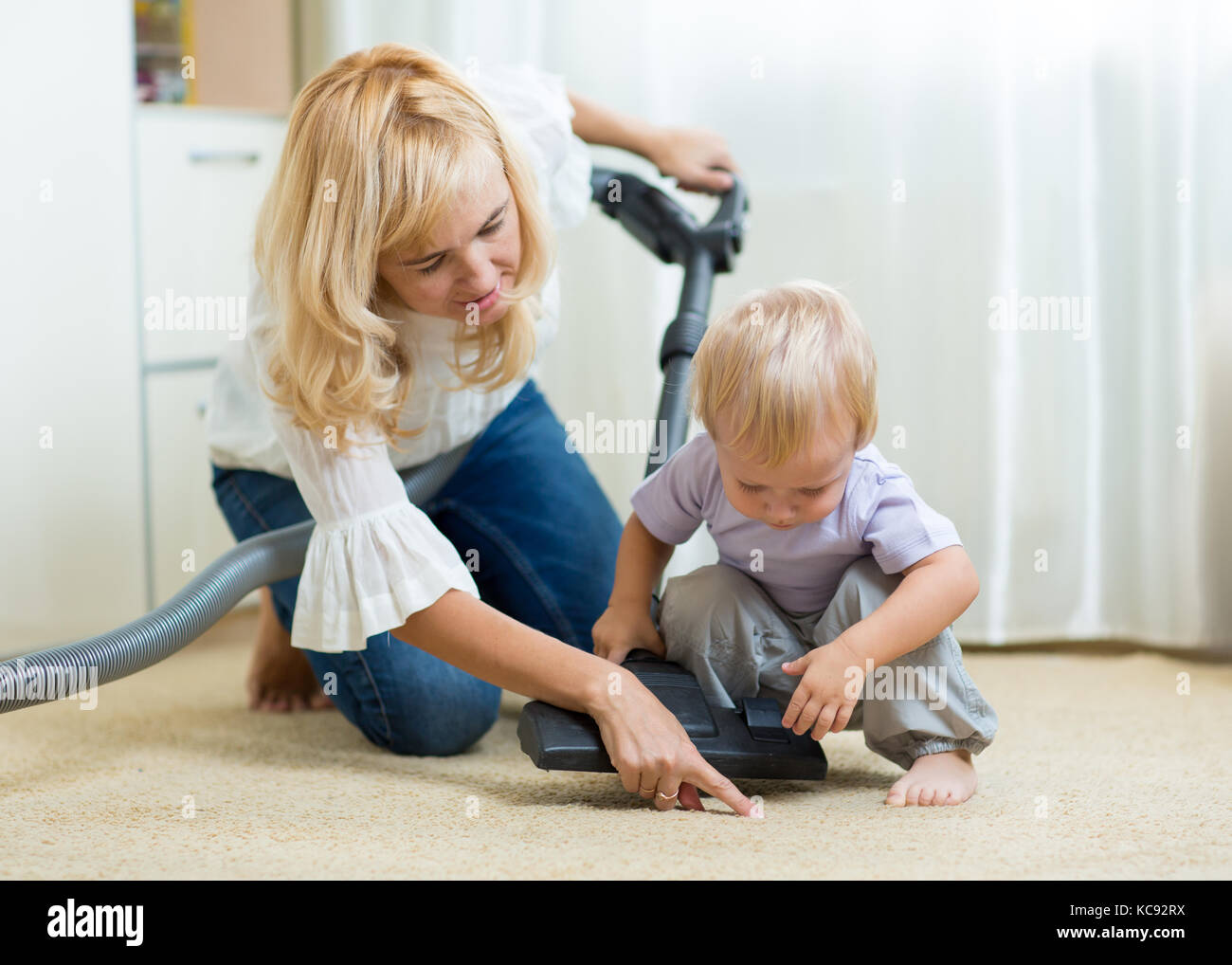 family mother and child boy cleaning the room with vacuum-cleaner - housework - Stock Image