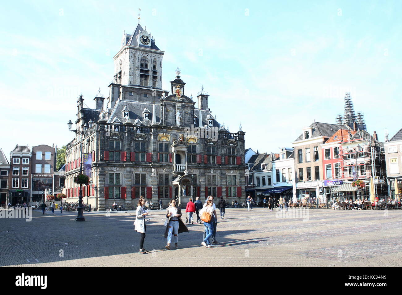 Young tourist girls in front of 17th century Renaissance style City Hall (Stadhuis) on the central Markt square - Stock Image