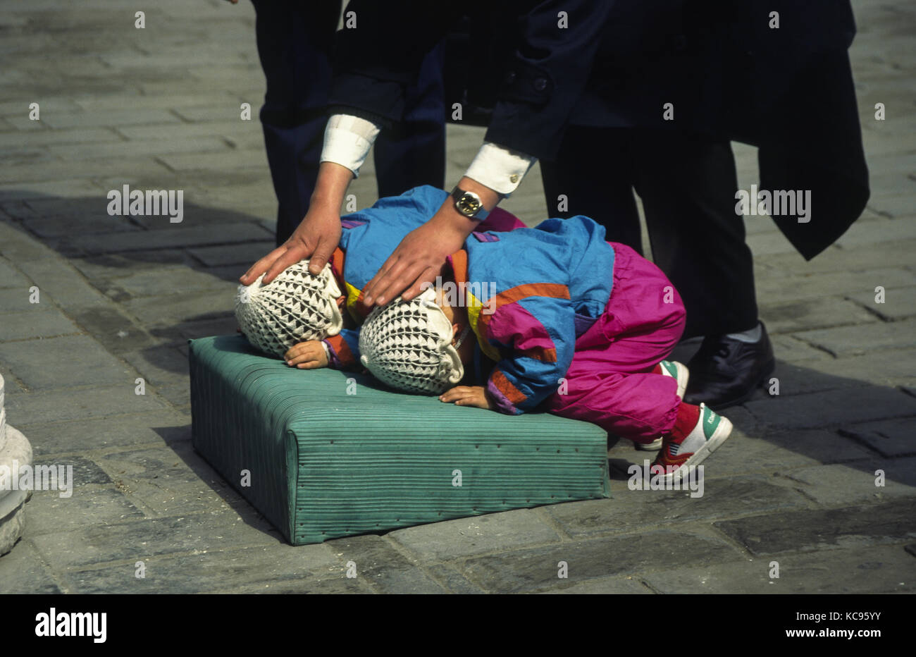 1995, Beijing, People's Republic of China, Asia - A father teaches his twins how to pray at a temple in Beijing. - Stock Image