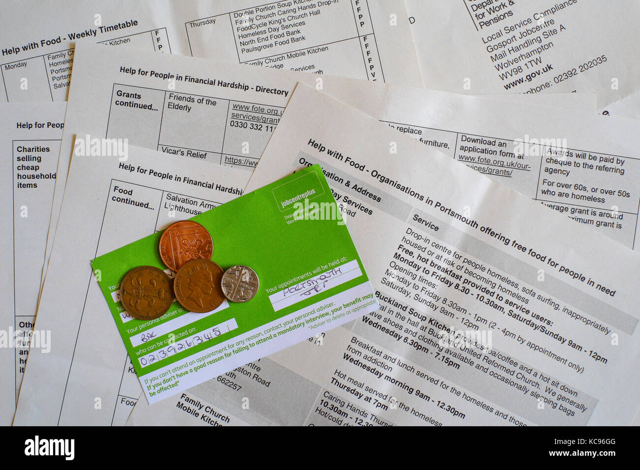 job centre signing on card with coins on top of papers showing food bank and charities details england uk - Stock Image