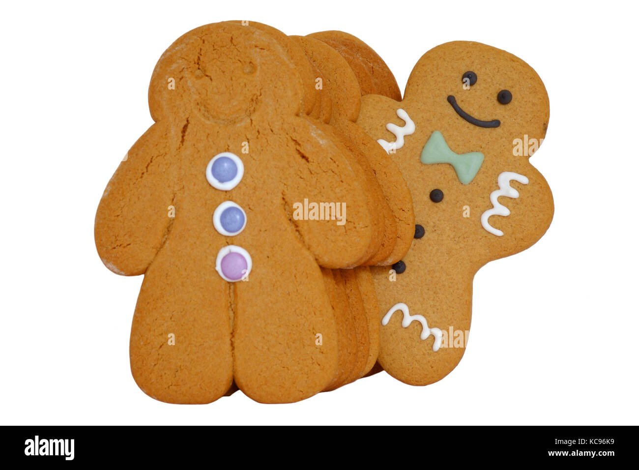 a line up of gingerbread men with one of them standing out of line cut out on white background - Stock Image