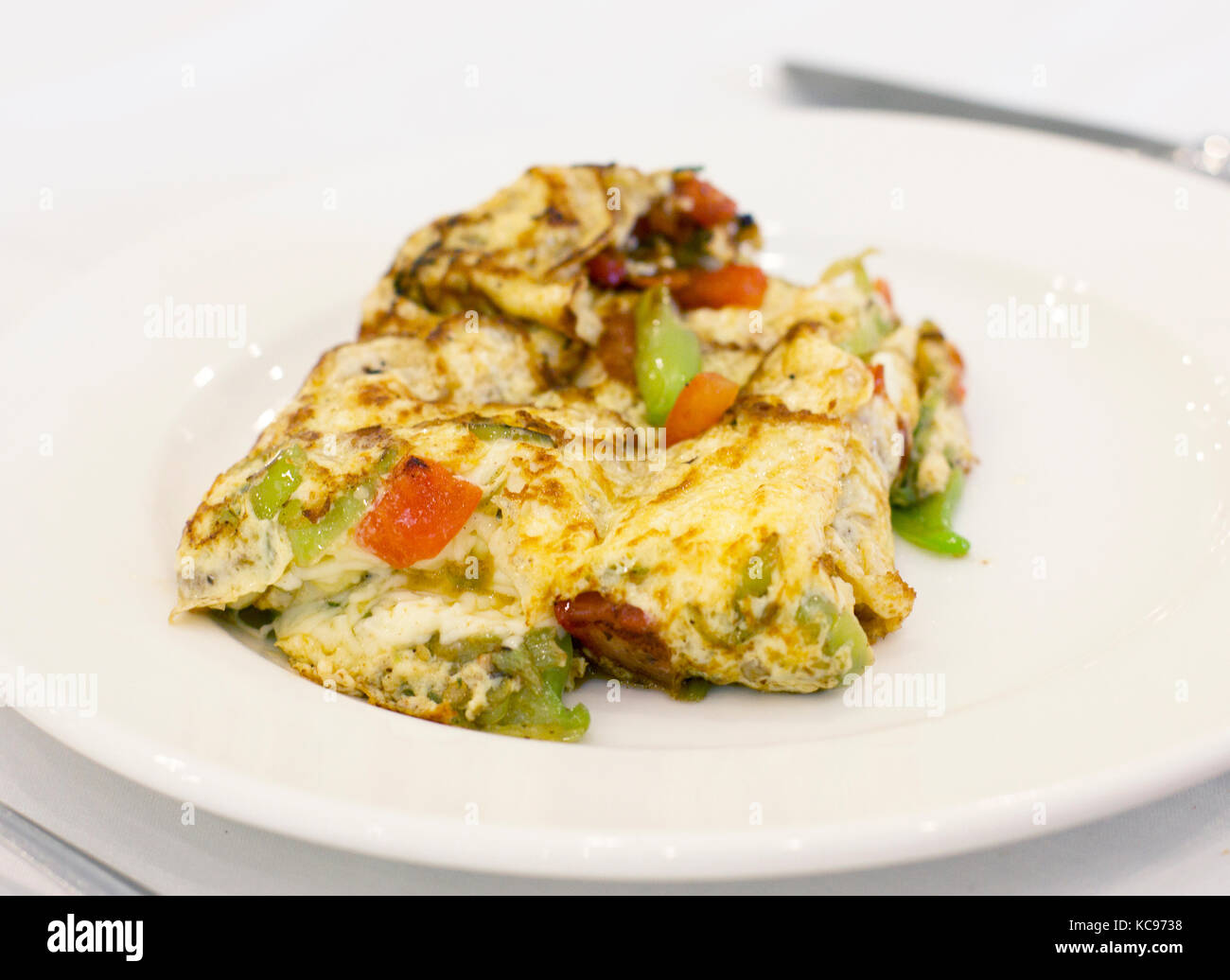Omelet with vegetables on the white porcelain plate - Stock Image