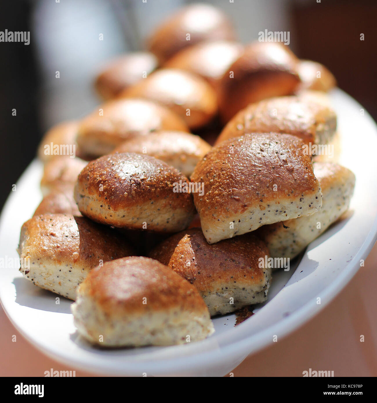 Freshly baked wheat buns with poppy seeds on the white plate - Stock Image