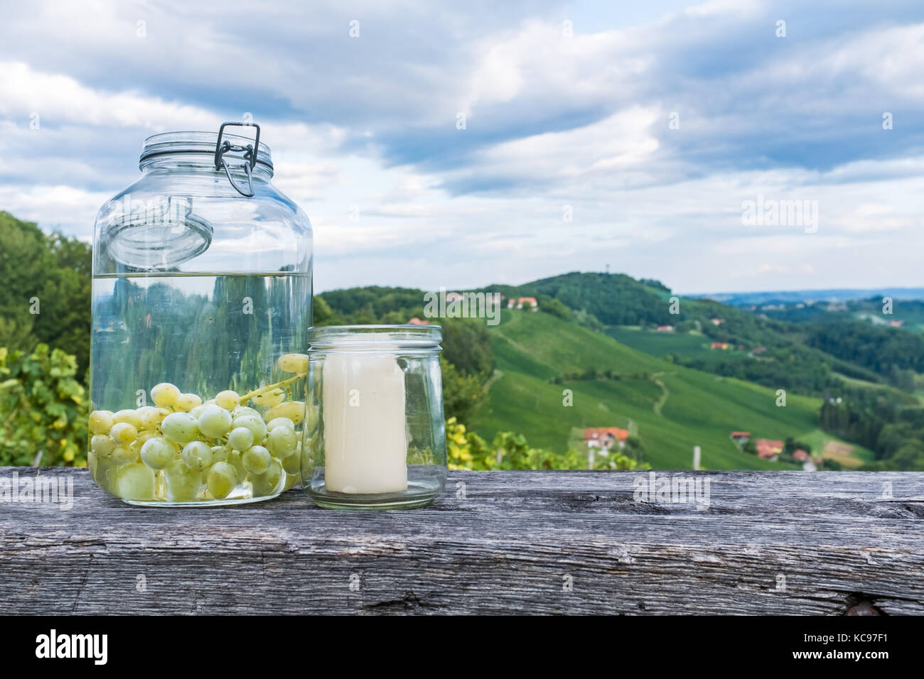 Jars with grapes and candle on wooden bench near vineyard along the south Styrian vine route in Austria, Europe - Stock Image
