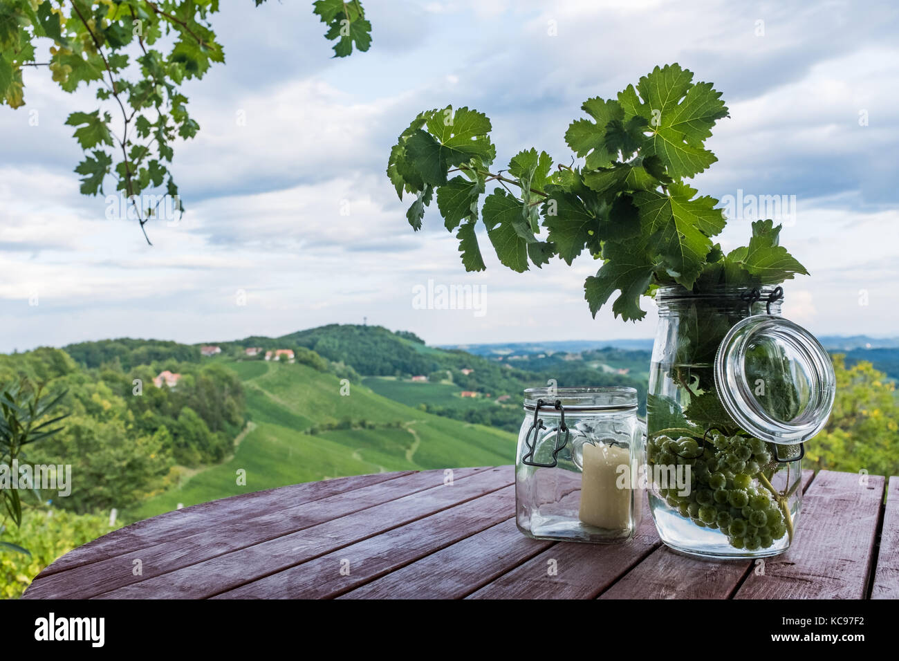 Jars with grapes and candle on wooden barrel near vineyard on south Styrian wine route in Austria - Stock Image