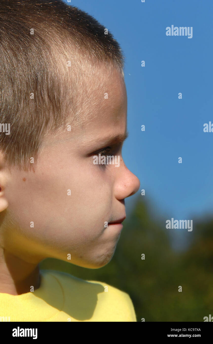 Little boy stars solemnly ahead, unsmiling, with his lips pursed.  He is not feeling well and is withdrawn and thoughtful. - Stock Image