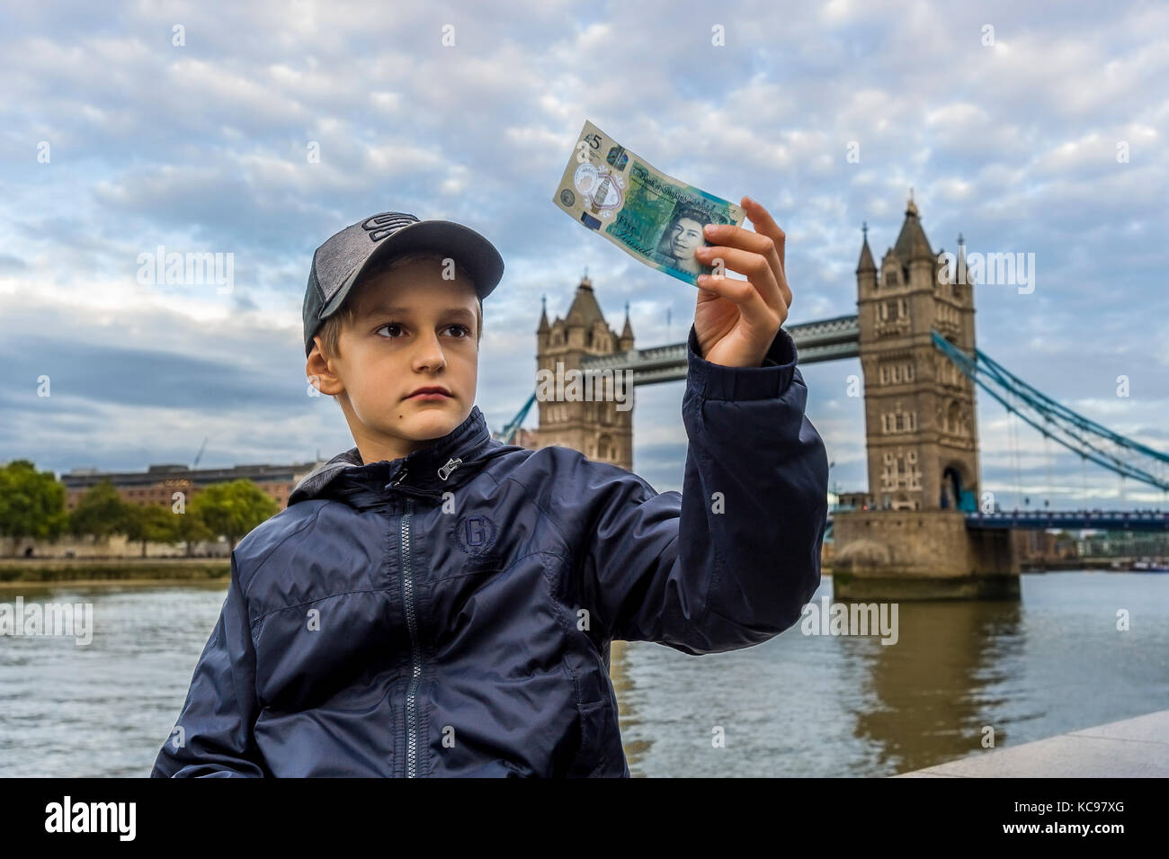 boy in baseball cap holding and looking at new british 5 pound banknote - Stock Image