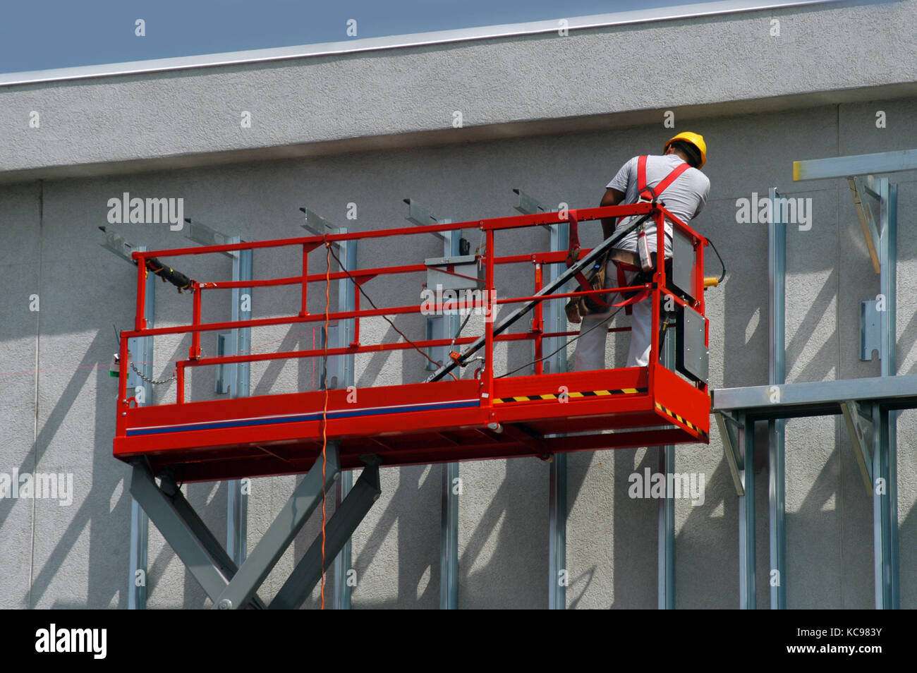 Worker is safely harnessed with safety straps to red lift, boom  He