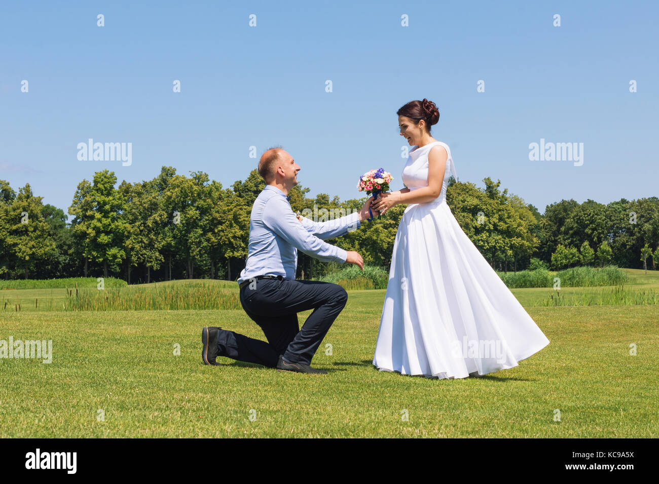 Man makes a proposal to his girlfriend to get married. Marriage proposal. Love and marriage concept. Young attractive - Stock Image
