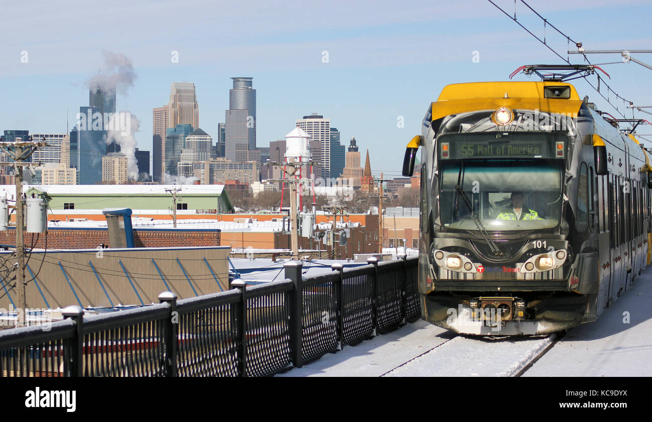 MINNEAPOLIS, MINNESOTA/UNITED STATES – JANUARY 15, 2011: A MCTO Lightrail train approaches a station with the skyline - Stock Image