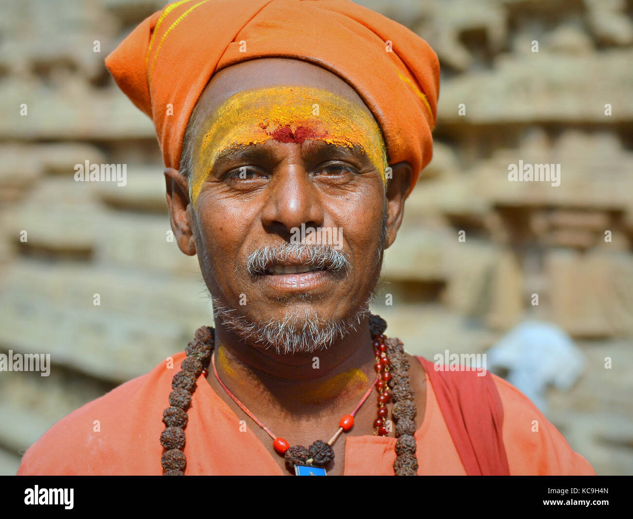 Middle-aged Shaivite sadhu with orange turban, red tilaka mark and yellow sandalwood paste on his forehead, rudraksha - Stock Image