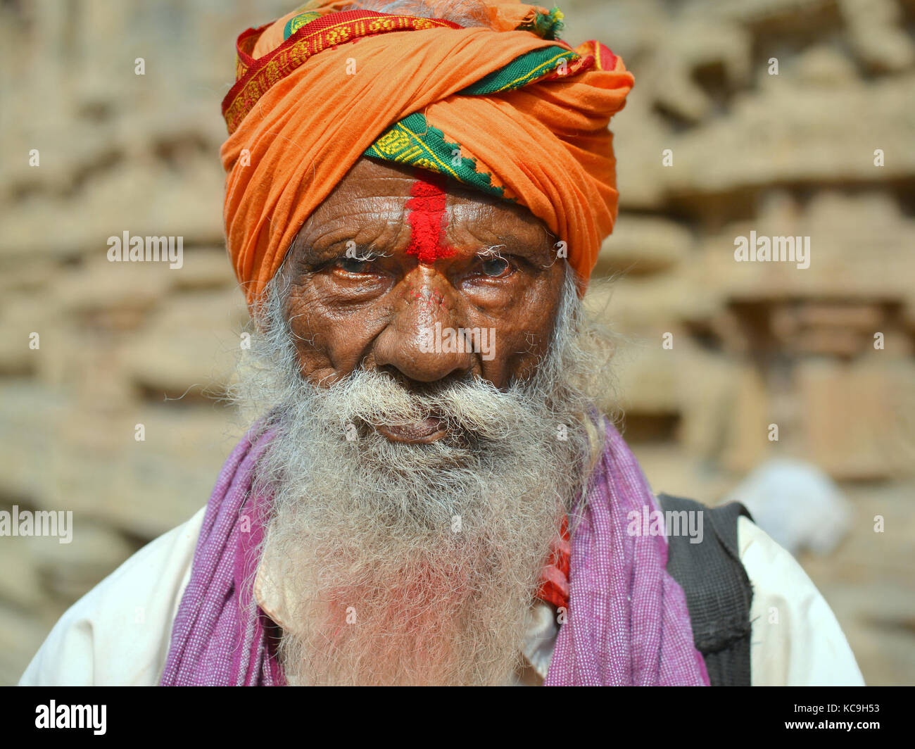 Very old Shaivite sadhu with orange turban and red tilaka mark on his forehead Stock Photo